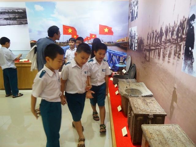 Các em học sinh thăm quan, tìm hiểu về những hiện vật trong không gian trưng bày tại khu di tích Tượng đài Mẹ VNAH.