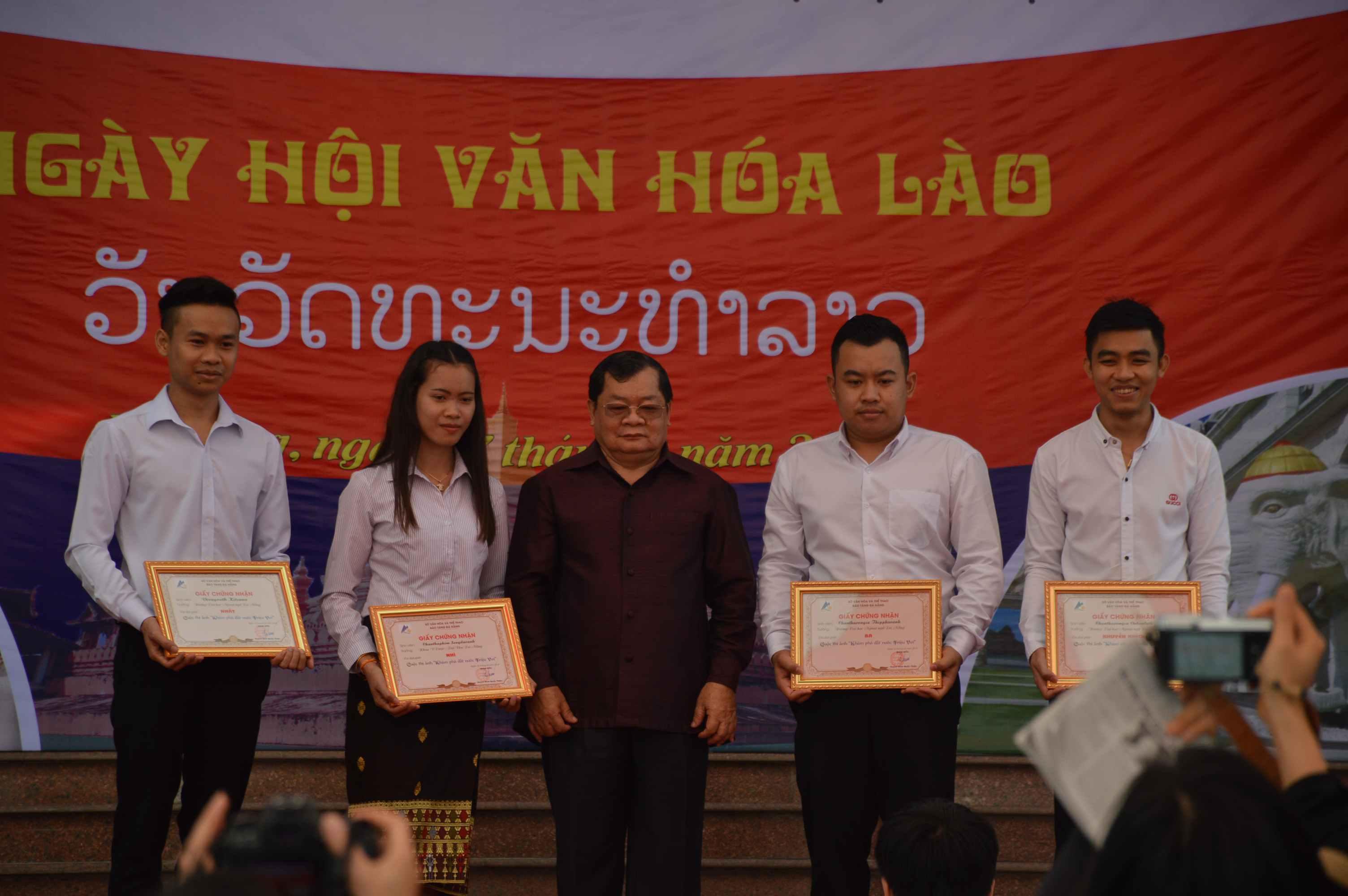 Tổng lãnh sự Lào tại TP.Đà Nẵng (giữa) trao giải cho 4 sinh viên đạt giải cuộc thi ảnh