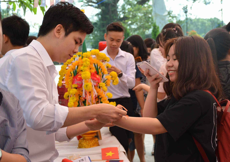 Một nam sinh viên Lào thắt chỉ cố tay (tập tục truyền thống của người Lào) cho nữ sinh viên Việt Nam. Ảnh: Q.T