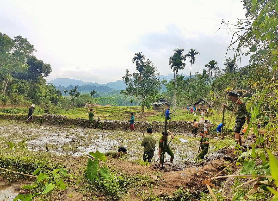 Cán bộ, chiến sĩ Công an huyện Nam Trà My đào ao nuôi cá cho người dân xã Trà Vinh. Ảnh: T.T