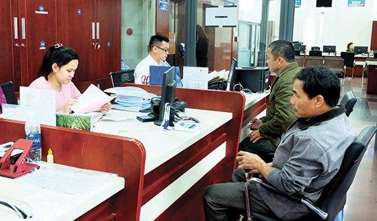 Công dân giao dịch giải quyết hồ sơ thủ tục tại Trung tâm Hành chính công và xúc tiến đầu tư Quảng Nam. Ảnh: VĂN HÀO