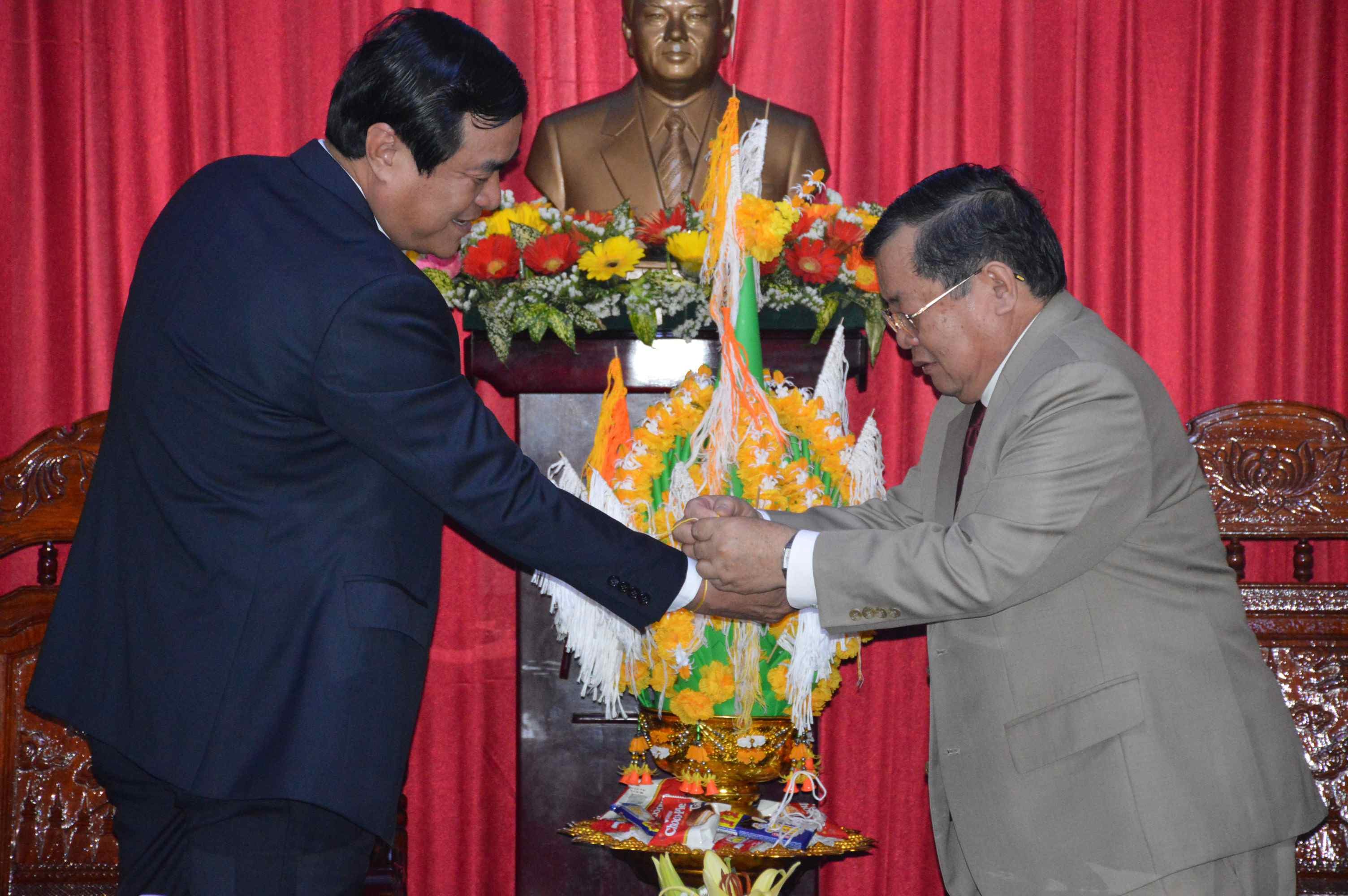 Consul General Phommaseng Khamsene (right) fastens the thread on Mr Cuong's wrist as a traditional ritual of Lao New Year