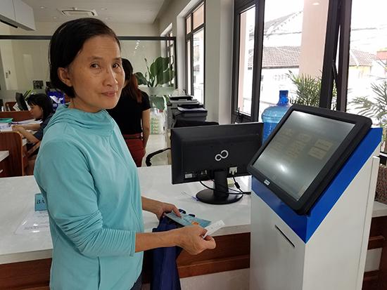 Công dân bấm phiếu lấy số thứ tự giao dịch tại Trung tâm HCC TP. Tam Kỳ. Ảnh: QUỐC TUẤN
