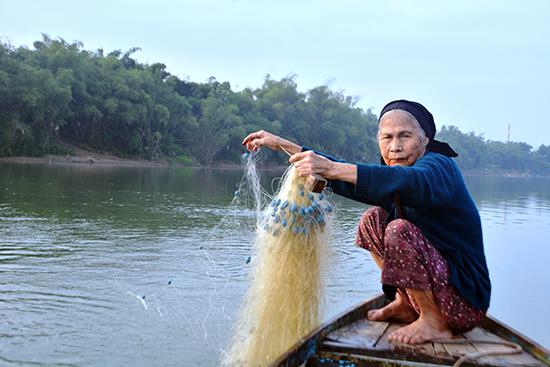 Mặc dù tuổi 80, nhưng bà Hoa vẫn đi thả lưới để đánh cá mòi. Ảnh: XUÂN THỌ