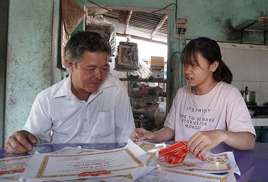 Huỳnh Xuân Diệu tự hào khoe với cha của mình về những thành tích đạt được qua các năm học. Ảnh: NHƯ TRANG