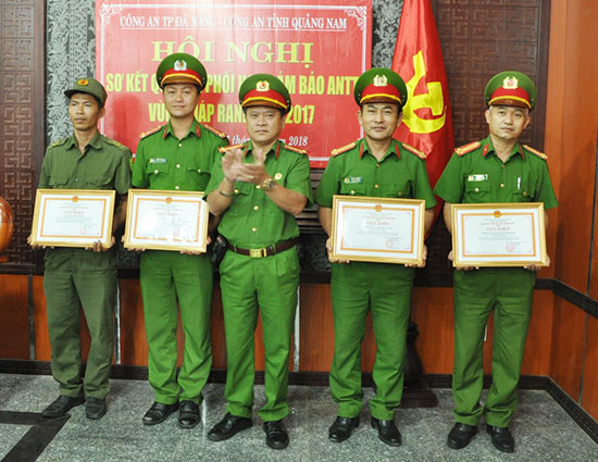 Đại tá Trương Quang Vinh - Phó Giám đốc Công an Quảng Nam trao giấy khen cho các tập thể, cá nhân có thành tích xuất sắc trong thực hiện quy chế phối hợp đảm bảo ANTT vùng giáp ranh. Ảnh: XUÂN MAI