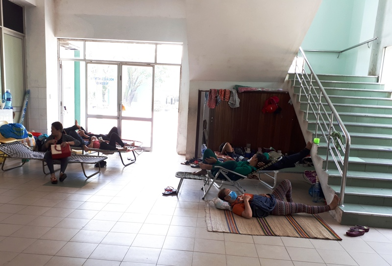 Người nhà bệnh nhân tìm những chỗ trống, thoáng mát ở hành lang, dưới cầu thang để trốn nóng, nghỉ ngơi. Ảnh: N.TRÚC