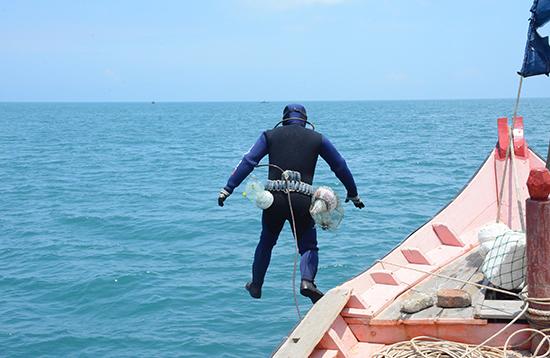 Thợ lặn gieo mình xuống nước, bắt đầu một đợt lặn bắt tôm nhí.Ảnh: P.G