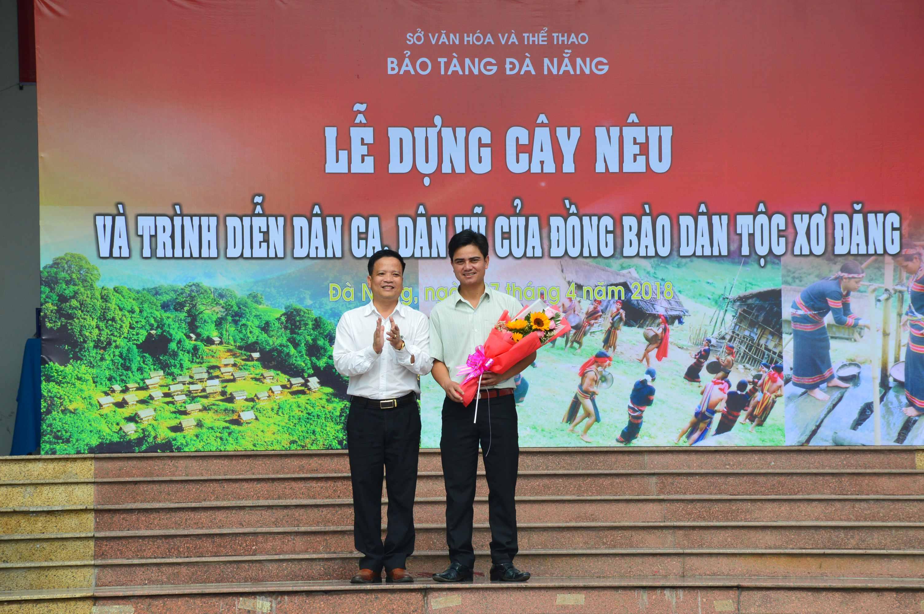 Lãnh đạo Bảo tàng Đà Nẵng tặng hoa lưu niệm cho ông Nguyễn Duy Phương - Chủ tịch UBND xã Trà Nam (phải). Ảnh: Q.T