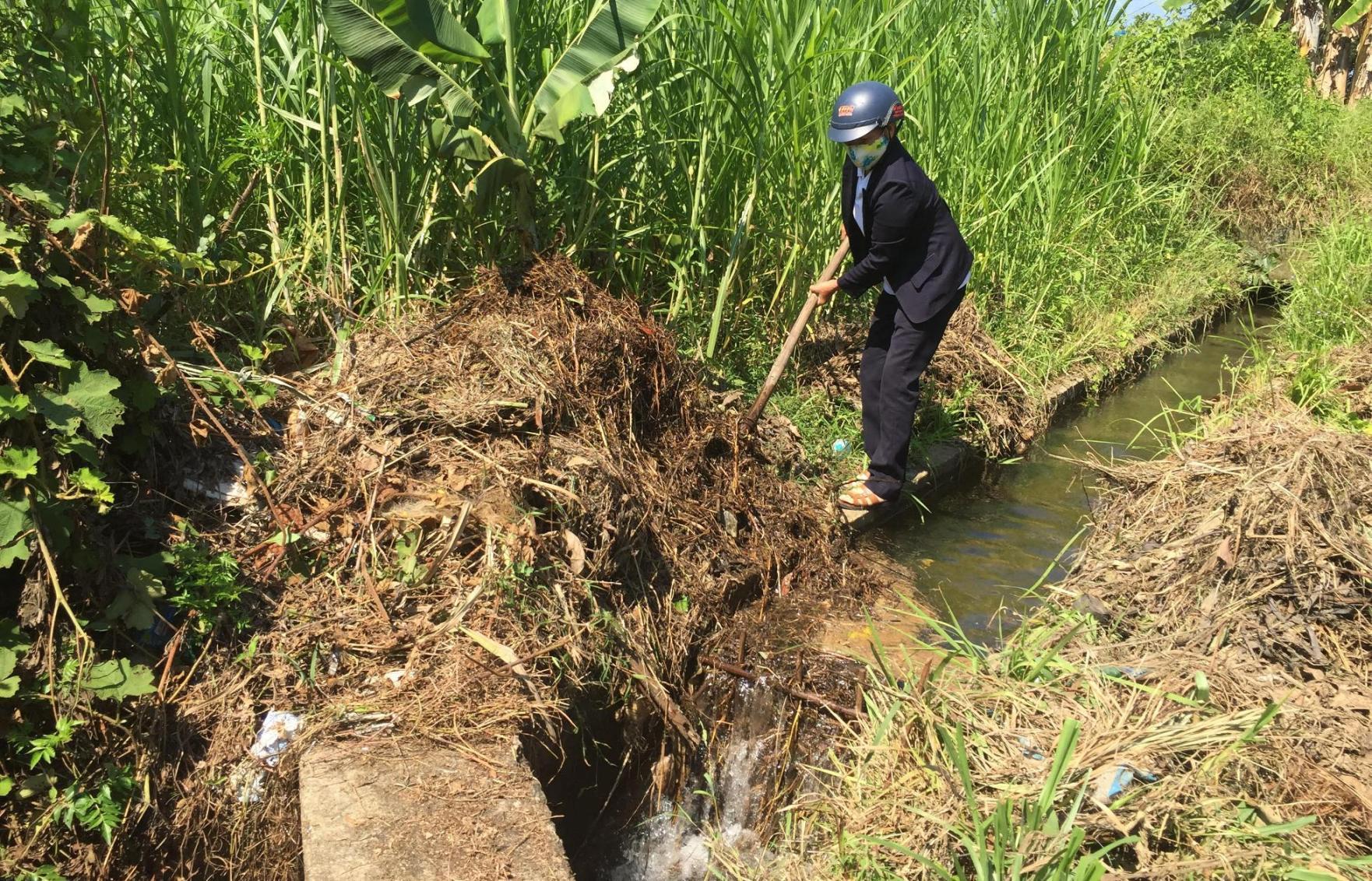 Cán bộ quản lý hồ chứa nhiều lúc phải đi vớt rác để thông kênh đưa nước xuống đồng.. Ảnh: PHAN VINH
