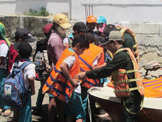 Bộ đội giúp học sinh mặc áo phao an toàn khi qua sông. Ảnh: V.P