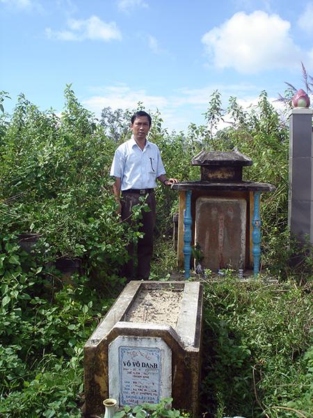 Mộ ông Nguyễn Phước Doãn - tiền hiền thôn Tứ Bàn. Người đứng bên mộ là hậu duệ. Ảnh: Phú Bình