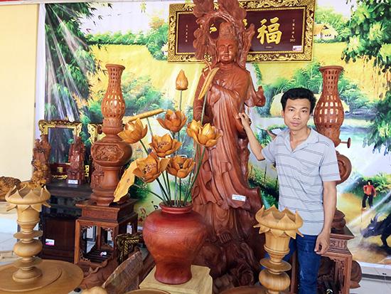 Anh Phan Phước Tuấn bên những sản phẩm do cơ sở Gỗ mỹ nghệ Gò Nổi chế tác. Ảnh: VĂN MẾN