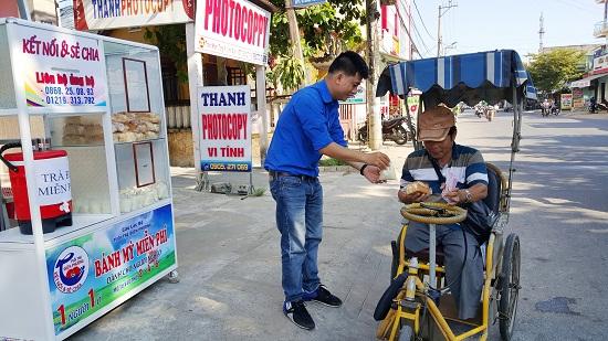 Phát bánh mì miễn phí cho người bán vé số dạo. Ảnh: CT