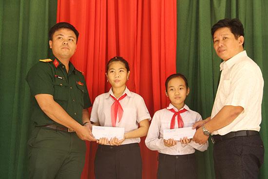 Đại diện Chi đoàn Cơ quan quân sự huyện Nam Giang trao quà hỗ trợ cho 2 học sinh nhận đỡ đầu. Ảnh: ALĂNG NGƯỚC