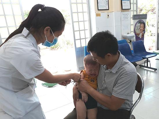 Đưa trẻ đi tiêm phòng tại Trung tâm Y tế dự phòng tỉnh. Ảnh: C.N