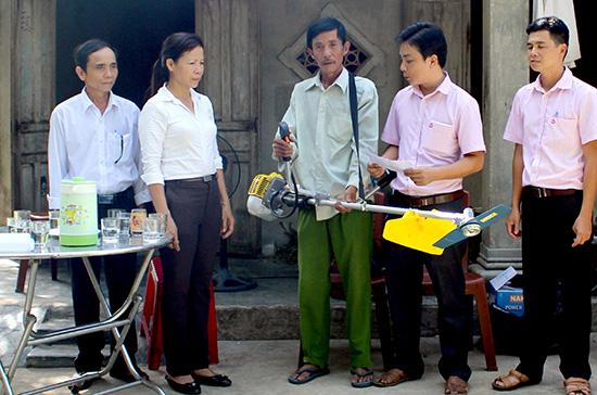 Chi bộ Phòng giao dịch Ngân hàng chính sách xã hội huyện Phú Ninh trao phương tiện sinh kế cho hộ nghèo. Ảnh: Ngọc Lâm
