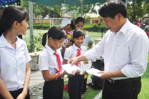 Ông Trần Phú Hòa-Giám đốc Công ty xây dựng Trung Trung Bộ tặng học bổng cho học sinh nghèo. Ảnh: T.V