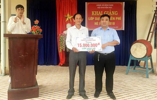 Ông Sự (bên trái) vui mừng nhận tiền hỗ trợ của Công ty CP Capella Quảng Nam trong buổi khai giảng lớp học hè. Ảnh: NVCC