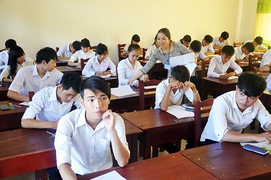 Giám thị phát giấy làm bài cho thí sinh tại kỳ thi THPT quốc gia 2017. Ảnh: X.PHÚ