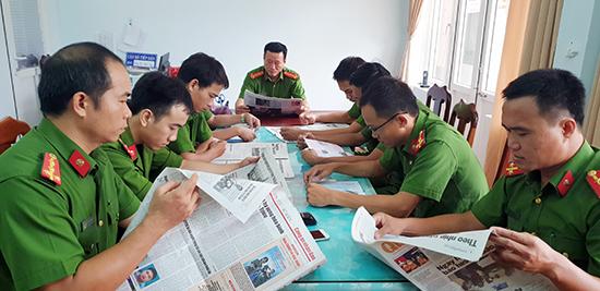 Đọc báo đầu giờ buổi sáng tại Công an phường Tân Thạnh, TP.Tam Kỳ. Ảnh: Q.SƠN