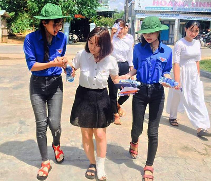 Em Nguyễn Thị Kim Thoa (Thăng Bình) bị đau chân được các tình nguyện viên đưa vào trường thi. Ảnh: T.T