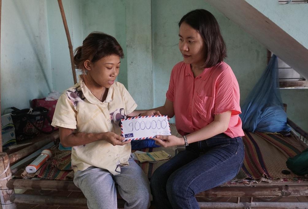 Tác giả bài viết trao số tiền 9 triệu đồng các nhà hảo tâm hỗ trợ Nguyễn Thị Cẩm Nhung. (ảnh: Bình Nguyên)