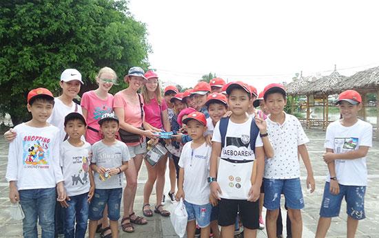 Nhóm học sinh Điện Bàn tặng quà du khách người Mỹ sau cuộc giao tiếp. Ảnh: NHƯ TRANG