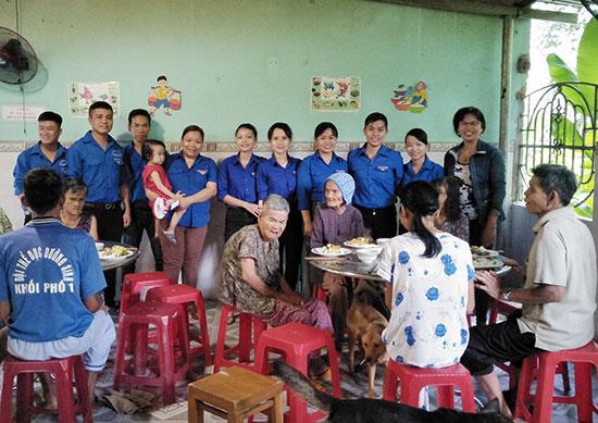 """Các bạn đoàn viên thị trấn Tân An với """"Bữa cơm gia đình"""" dành cho các cụ già tại Trung tâm Dưỡng lão Hiệp Đức. Ảnh: N.THU"""