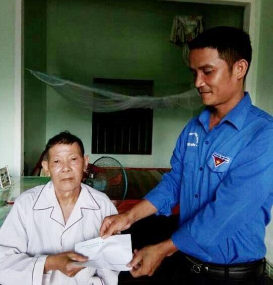 Anh Huỳnh Văn Đức - Bí thư Chi đoàn thôn 4 Tiên Sơn tặng quà người có công nhân dịp 27.7. Ảnh: H.L
