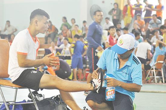 Săn sóc viên đang xịt nước lau giày cho VĐV môn đẩy gậy trước khi vào thi đấu.