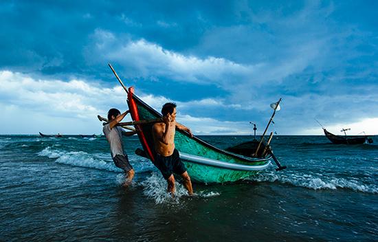 Ngư dân đưa thuyền lên bờ.