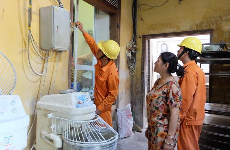 Giúp người dân vệ sinh hệ thống điện và hướng dẫn sử dụng điện an toàn. Ảnh: M.L