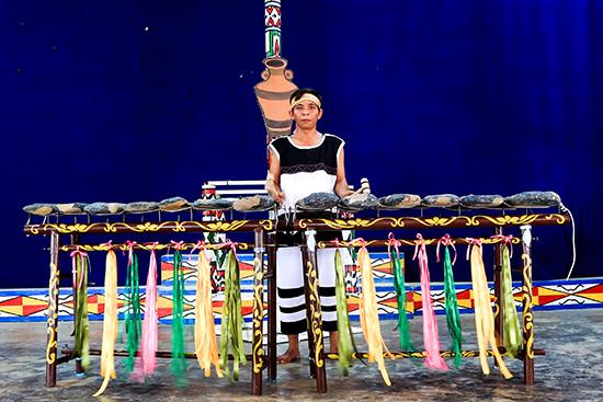 Nghệ nhân Raglai (ở Khánh Hòa) bên bộ nhạc cụ đàn đá truyền thống của dân tộc mình. Ảnh: QUỐC NGUYỄN