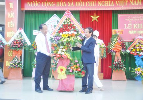 Chủ tịch UBND tỉnh Đinh Văn Thu tặng lẵng hoa chúc mừng khai mảng năm học mới cho Trường THPT chuyên Nguyễn Bỉnh Khiêm. Ảnh: X.P