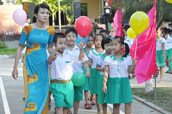 Học sinh đầu cấp được cô giáo dắt vào trường ngày khai giảng. Ảnh: X.PHÚ