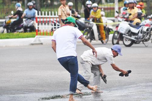 Đêm trước mưa khá to nên đường đua đoạn vòng xoay ngã năm trước Đài Phát thanh truyền hình Quảng Nam còn đọng nước. Để giúp an toàn cho cuộc đua, một số khán giả tự nguyện tát nước để làm khô mặt đường. Ảnh: T.V