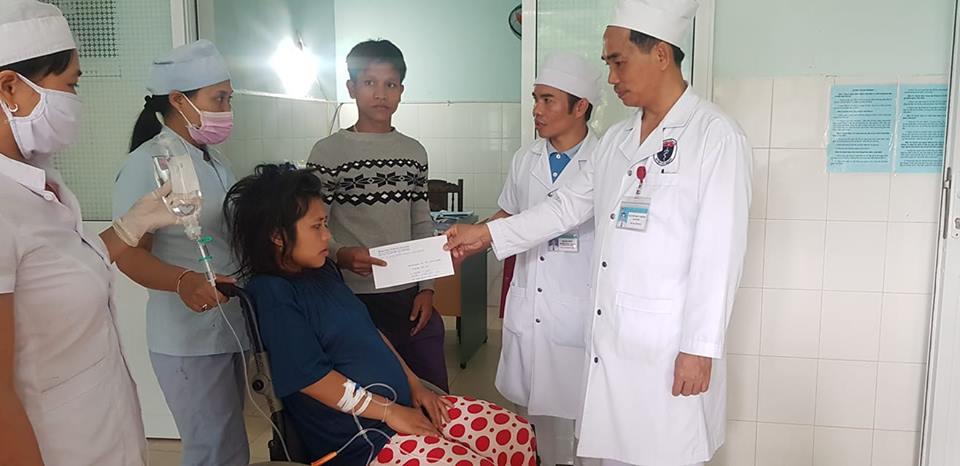 Đại diện trung tâm y tế huyện Tây Giang trao tiền hỗ trợ cho bệnh nhân In. Ảnh: H.T