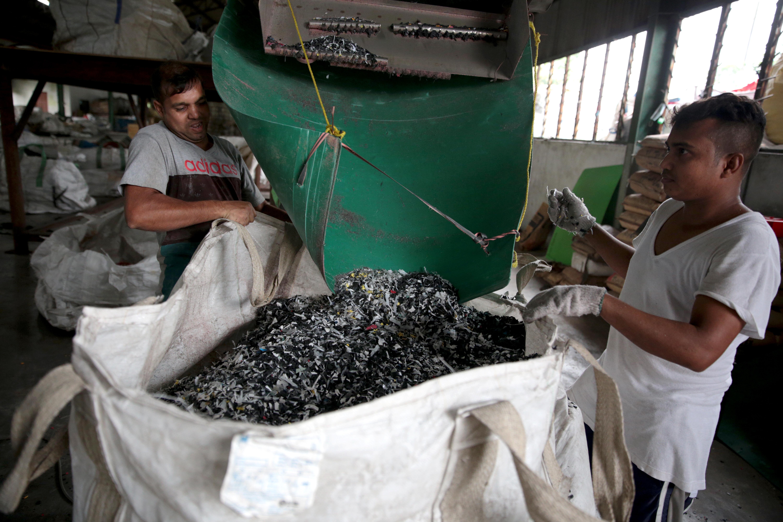 Các công nhân thu gom nhựa được nghiền nát từ máy tại cơ sở của V1 Recycle. Chất thải nhựa được nghiền thành dạng hạt hoặc mảnh để chế biến tiếp và xử lý dễ dàng hơn.