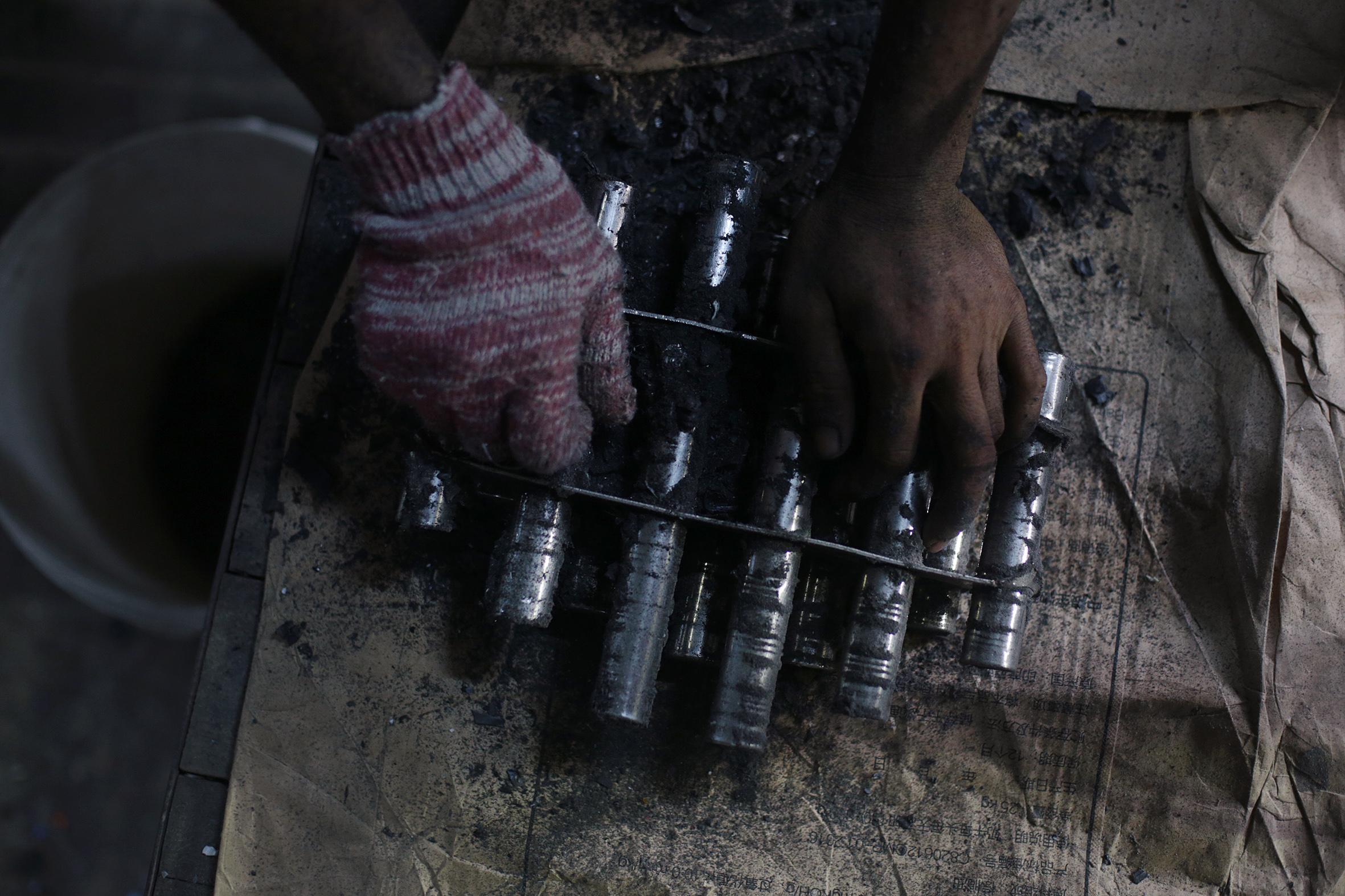 Một công nhân loại bỏ kim loại từ một nam châm được sử dụng trong một máy nghiền nhựa. Nam châm được lắp đặt trong các máy nghiền của cơ sở để đảm bảo rằng nhựa tái chế không có tạp chất kim loại trước khi chuyển sang giai đoạn tiếp theo của quá trình tái chế.