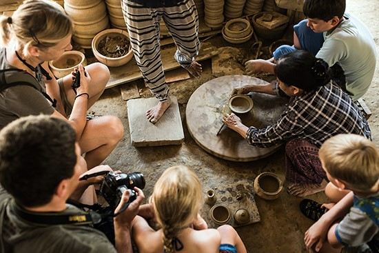 Foreign tourists are impressed by the techinique of making pottery in Thanh Ha village.