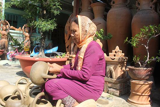 Bà Đàng Thị Phan đang hoàn thành một sản phẩm gốm. Ảnh: TRẦN ĐĂNG