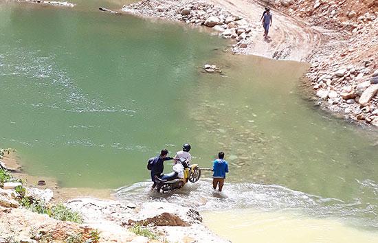 Đến với các bản của huyện Kà Lừm phải lội bộ, khiêng xe qua sông suối.  Ảnh: ĐÌNH HIỆP