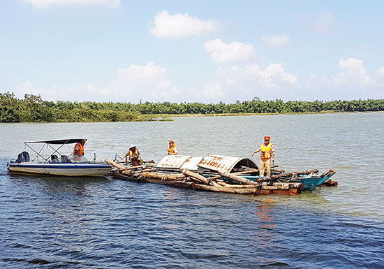 Lực lượng Cảnh sát đường thủy vận chuyển số gỗ tang vật bắt giữ được vào sáng 20.10 bàn giao cho cơ quan chức năng. Ảnh: T.C