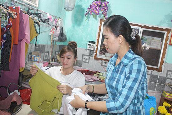Chị Nguyễn Thị Mỹ Lệ (bìa phải) trao đổi với lao động cách may mẫu áo mới. Ảnh: D.L
