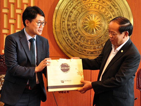 Director Sungnnung Lee (left) offers a gift (South Korean ginseng) to Chairman Thu.