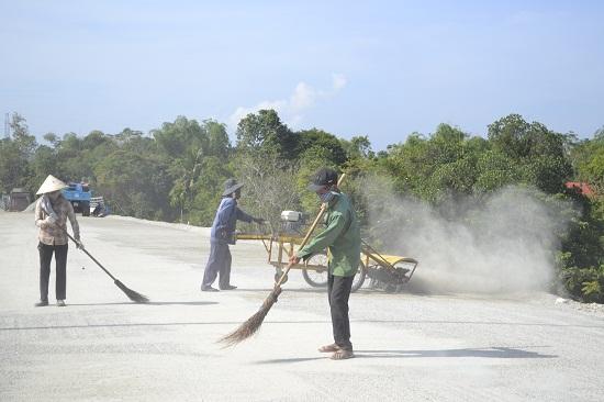 Thổi bụi, vệ sinh bề mặt cấp phối đá dăm trước khi tưới nhũ tương và thảm bê tông nhựa. Ảnh: CT