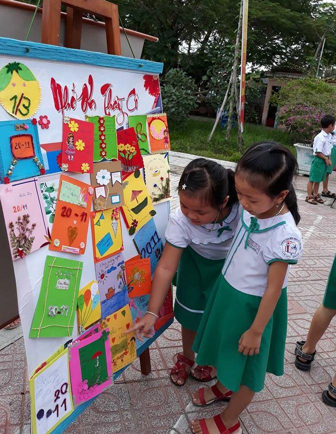 Học sinh Trường Tiểu học Nguyễn Văn Trối (Tam Kỳ) xem trưng bày thiệp tự làm. Ảnh C.N