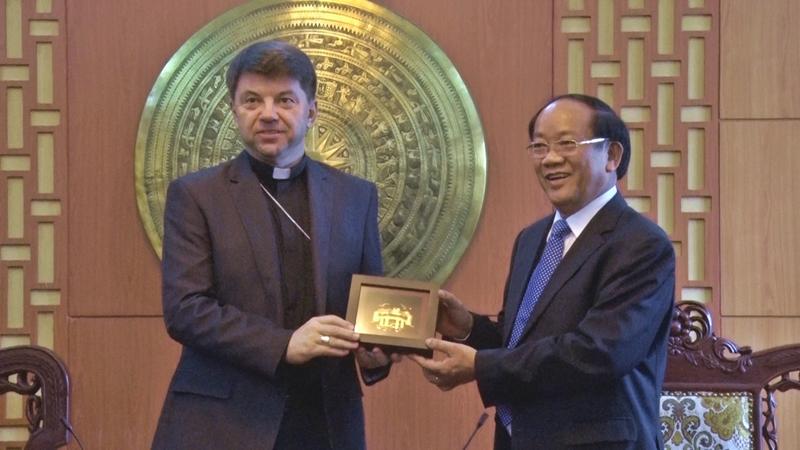 Chairman Dinh Van Thu (R) gives Archbishop Marek Jalewski a souvenir.