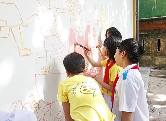 Học sinh Trường Tiểu học Trần Quốc Toản (Tam Kỳ) vẽ tranh trên tường trường. Ảnh C.N